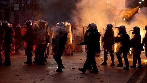 Un grupo de antidisturbios se portegen de los ataques