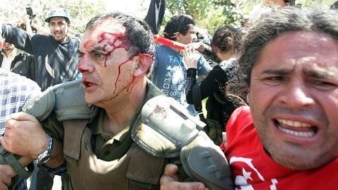 Un carabinero es ayudado tras ser atacado por los manifestantes marcha