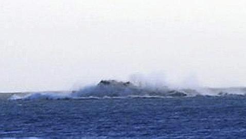 Imagen de una columna de vapor con ceniza en el mar