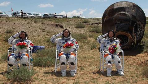 Los tres astronautas chinos y la cápsula tras su aterrizaje en una pradera de Mongolia Interior