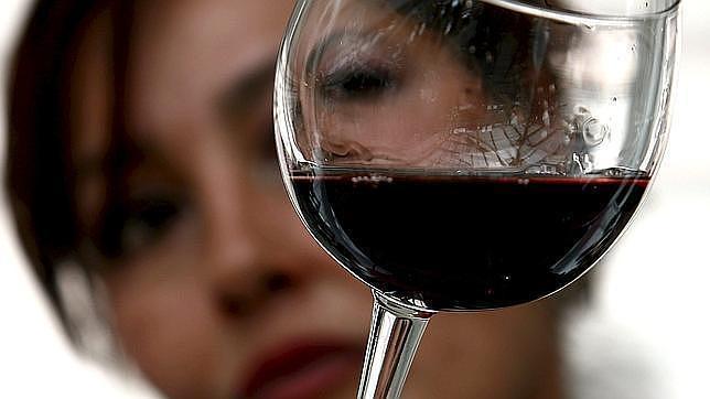 Una mujer observa una copa de vino tinto for Copa vino tinto