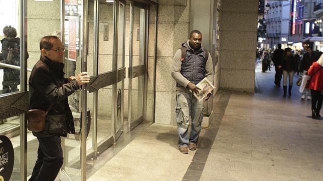 Un inmigrante vende su periódico en la puerta de unos grandes almacenes de Preciados