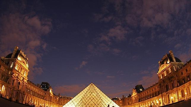 Una imagen nocturna de la entrada del Museo del Louvre, en París