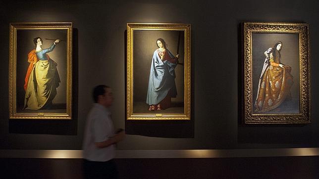 Un hombre pasa ante tres cuadros de Zurbarán en el antiguo convento de Santa Clara