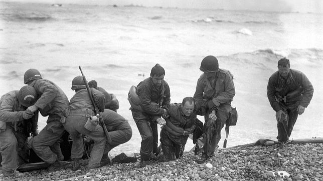 Naufragos del día D, algunos soldados son ayudados a salir del agua, agotados