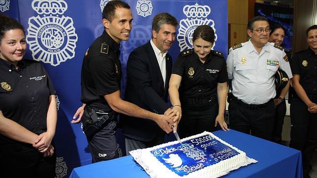 Ignacio Cosidó, director general de la Policía, corta la tarta conmemorativa ayudado por dos agentes