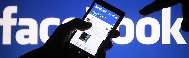 Un usuario muestra un teléfono donde se puede apreciar Facebook