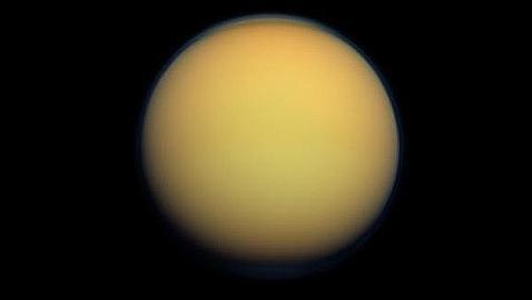 Titán, envuelta por una gruesa capa de atmósfera naranja