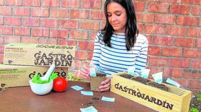 La joven Lola Burón con los pequeños huertos seleccionando plantas aromáticas
