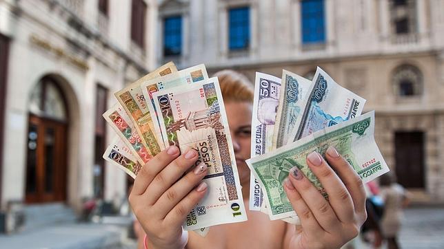 Una mujer muestra la doble moneda que circula por el país