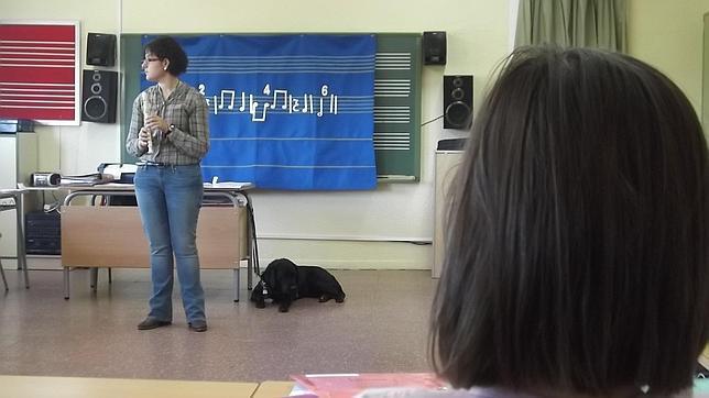 La imagen muestra a la maestra con una flauta en la mano y el perro guía junto a ella