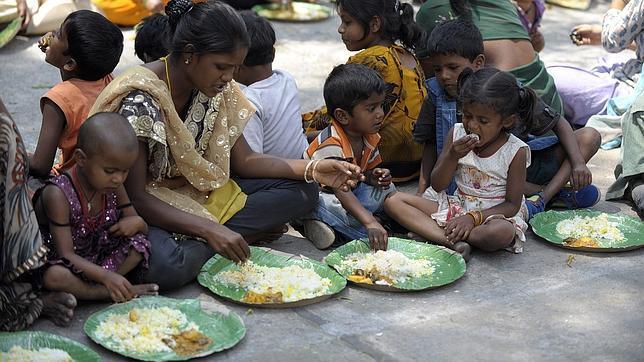 Personas sin hogar en la India comen a través de un programa alimentario