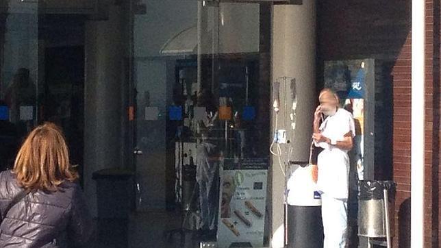 Un paciente con sonda y fumando en la puerta de un hospital
