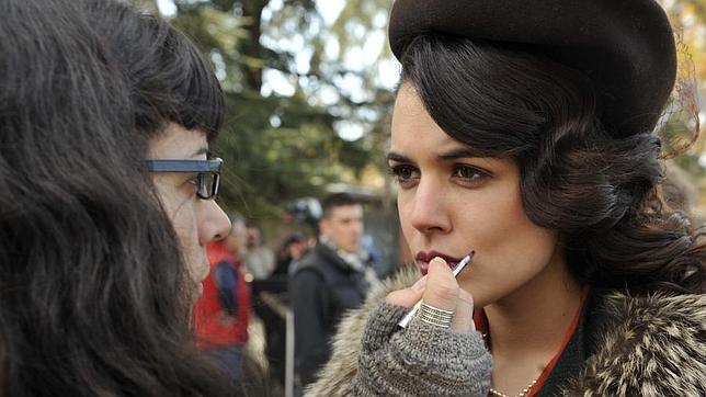 Una maquilladora retoca el maquillaje a Adriana Ugarte durante un rodaje en exteriores