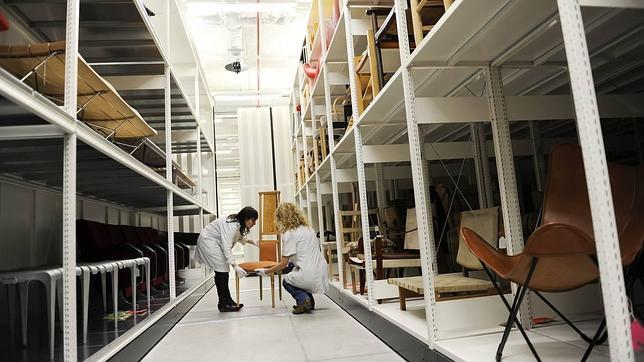Dos trabajadoras colocan mobiliario en el almacén del museo
