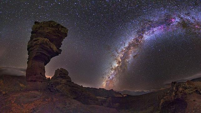 La Vía Láctea cruza el horizonte sobre el Teide, con el Roque Cinchado, o Árbol de Piedra, a su izquierda