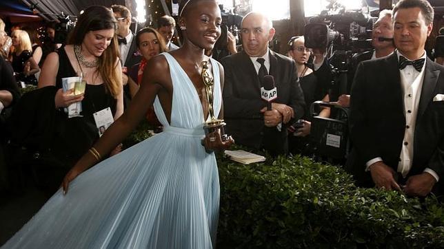 Lupita Nyong'o a la salida de los premios del cine, estatuilla en una mano y la cola de su vestido en otra