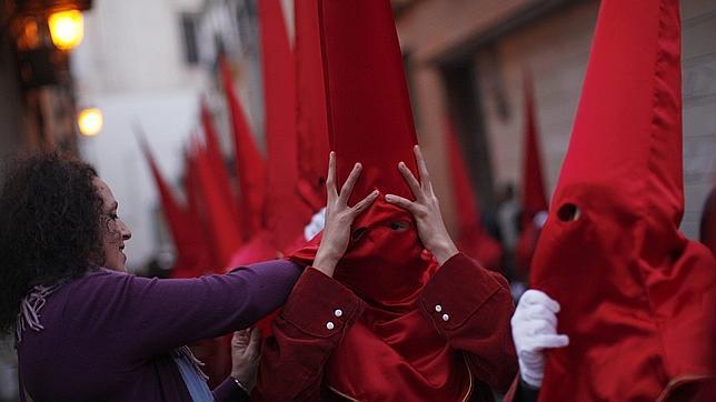 Una mujer ajusta el capirote a un penitente durante la Semana Santa de Málaga