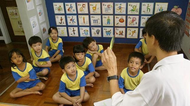 Un profesor junto a sus alumnos en un centro educativo en Singapur