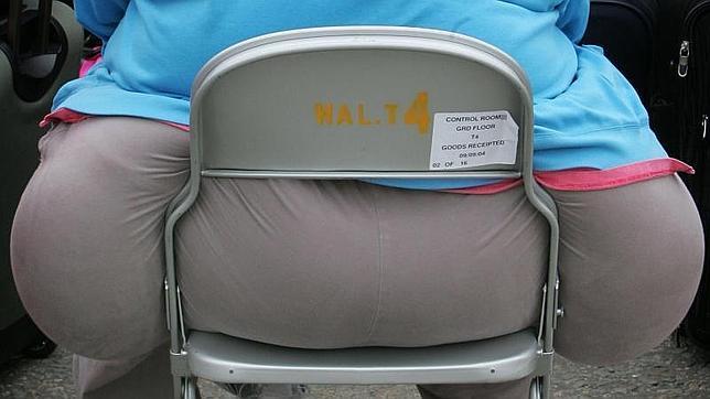 Una mujer obesa espera en un aeropuerto de Londres