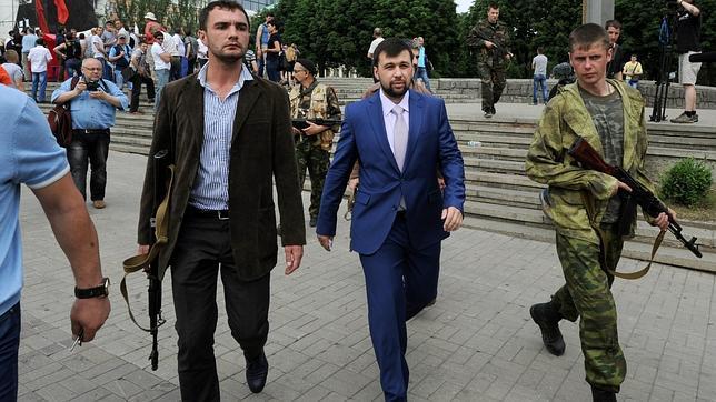 Hombres armados escoltan en Donetsk a Denis Pushilin, portavoz de los rebeldes