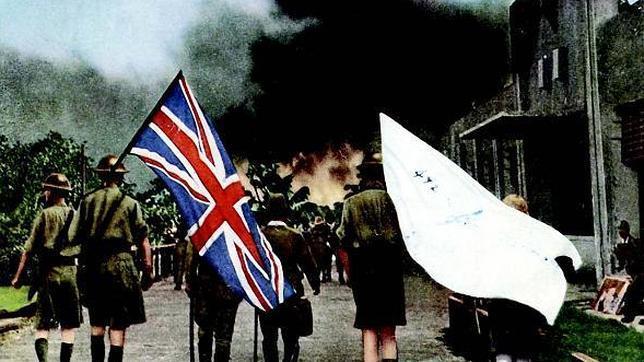 Oficiales británicos, que portan la bandera del Reino Unido y una enseña blanca, son conducidos por militares japoneses en el acto de rendición de Singapur