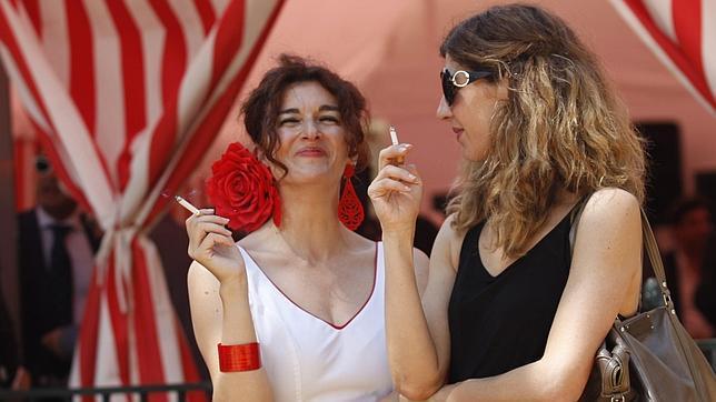 Dos mujeres fuman en Sevilla en la puerta de una caseta
