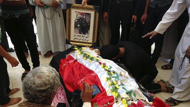 Varios iraquíes lloran junto al cadáver de un soldado iraquí asesinado