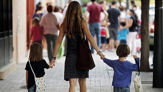 Una madre se dirige con sus hijos al colegio