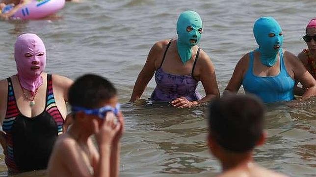 Mujeres en la playa de Qingdao, luciendo el «bikini facial»