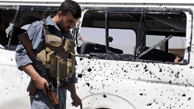 Un agente de seguridad armado inspecciona el lugar donde se produjo un atentado en Afganistán