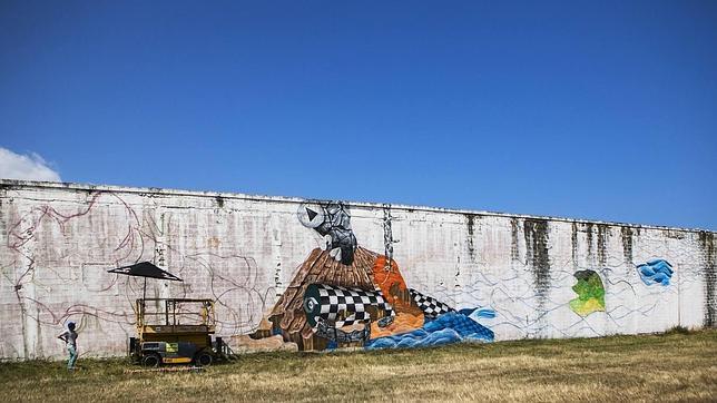 Obie Platon durante la ejecución de su mural en una antigua fábrica maderera