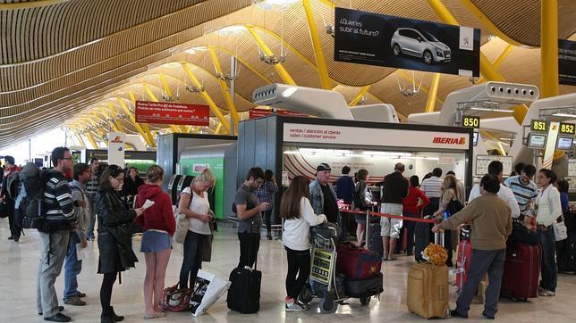 Viajeros esperando en la zona de facturación de la Terminal 4 del aeropuerto de Barajas