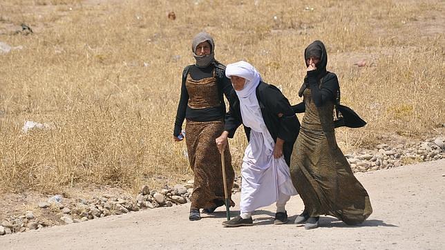 Mujeres yasidíes caminan por las afueras de la ciudad de Sinjar, recién tomada por el EI
