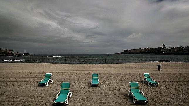 Hamacas vacías en una playa bajo la persistente amenaza de lluvia