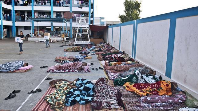 Un grupo de palestinos duerme en las inmediaciones de una escuela de la ONU en Gaza