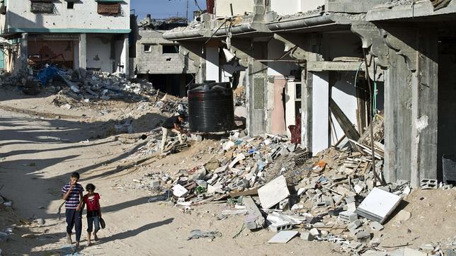 Dos muchachos pasean por una devastada calle de Shejaiya, en Gaza