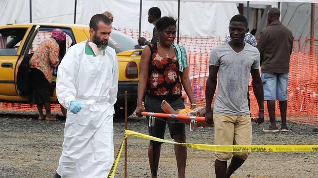 Personas transportando a un niño enfermo hacia el hospital en Monrovia