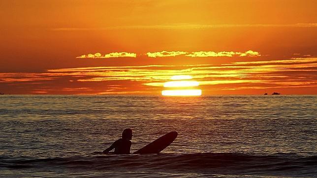 Un surfista disfruta del atardecer hoy en la playa de La Zurriola de San Sebastián