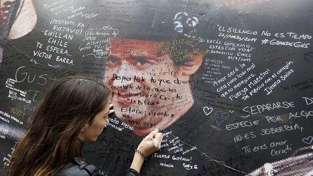 Una mujer escribe una dedicatoria en el mural colocado frente al hospital en el que estaba ingresado el cantante.
