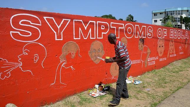Un grafitero dibuja los síntomas del ébola en una pared en Liberia
