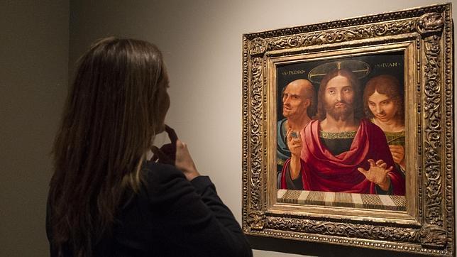 Una mujer admira «Salvator Mundi entre san Pedro y san Pablo», de Yáñez de la Almedina