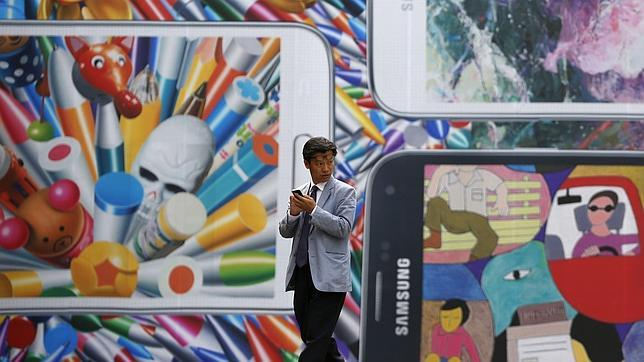 Un hombre pasa frente a un anuncio del Galaxy S5
