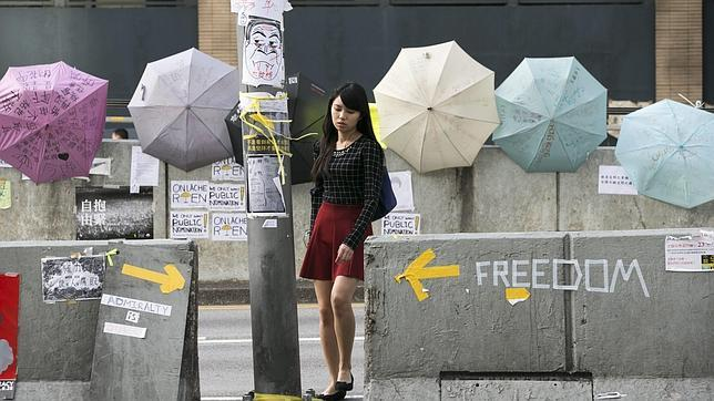 Una mujer de camino al trabajo pasa por una calle bloqueada en Hong Kong