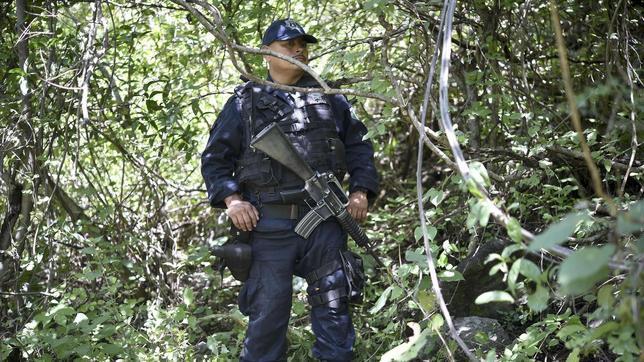 Un agente en el lugar donde han sido halladas las fosas con los cadáveres