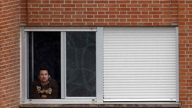 El marido de la auxiliar infectada de ébola en España, Javier Limón, asomado este martes en la ventana de su habitación en el Hospital Carlos III de Madrid