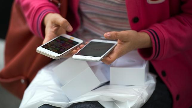 Una usuaria, con dos modelos de teléfono inteligente
