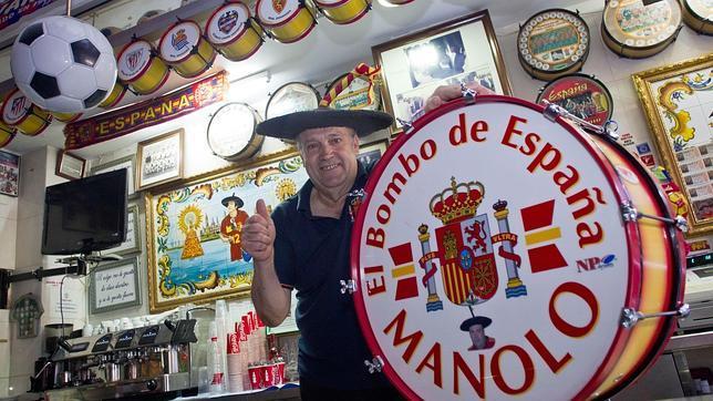 Manolo posa, con su característica boina y su bombo, en su bar de Valencia