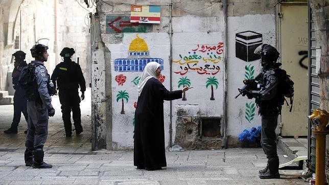 Una mujer palestina se dirige a los agentes israelíes que patrullan la ciudad vieja de Jerusalén