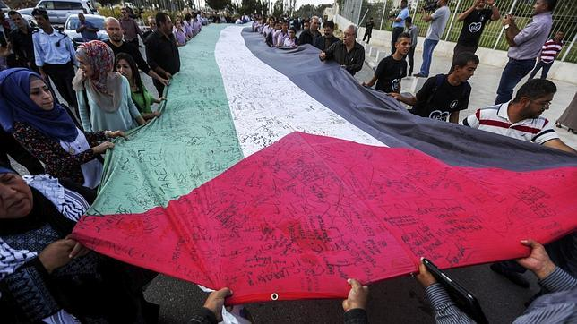 Palestinos sostienen una bandera en el décimo aniversario de Arafat